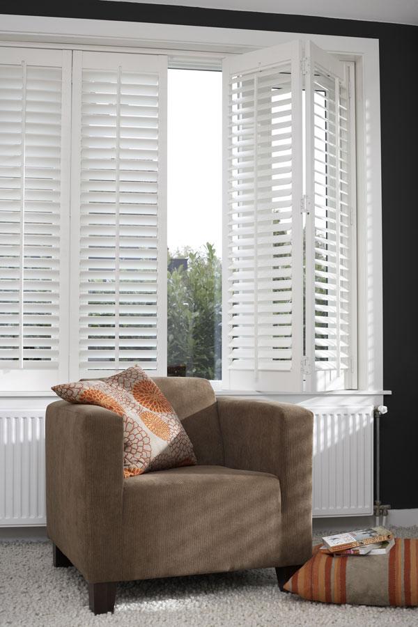 Shutters in woonkamer met bruine stoel