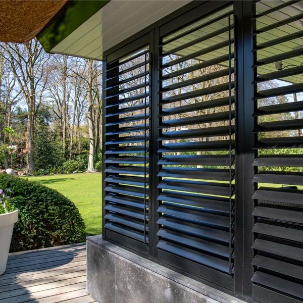 Zwarte buiten shutters in veranda met groene tuin