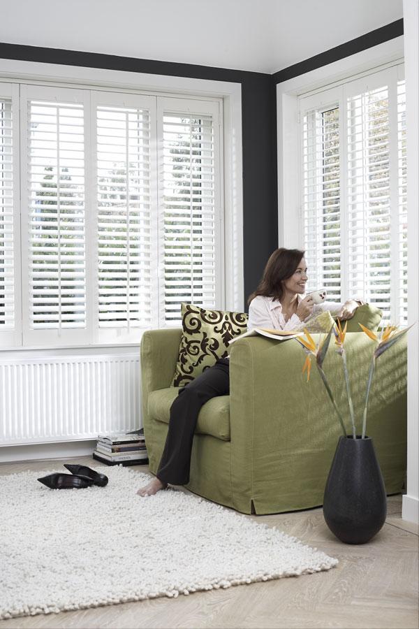 Shutters in woonkamer met groene stoel